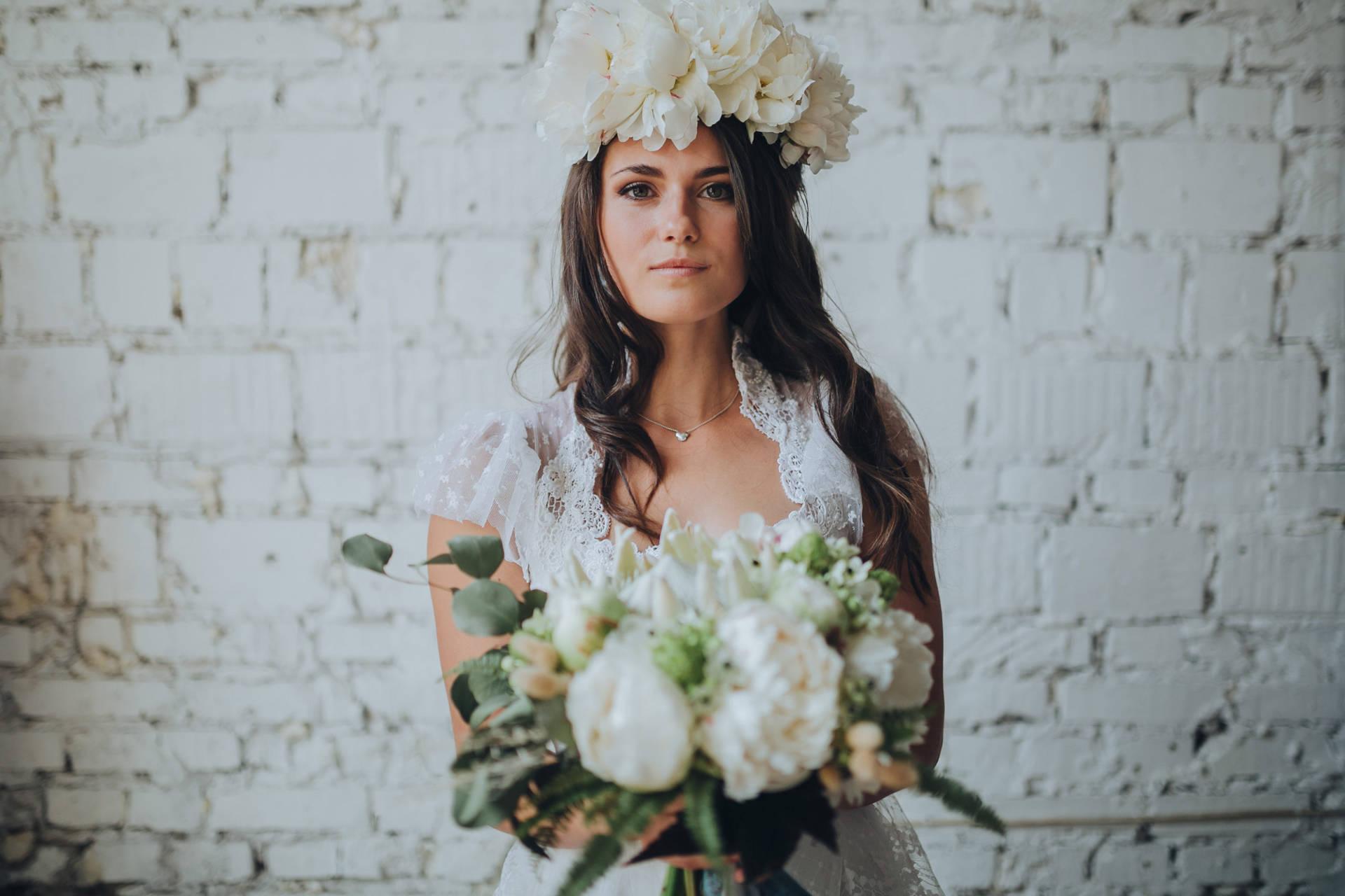 Braut mit Blumenstrauss vor weisser Wand